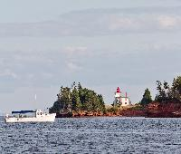 A lighthouse at the mouth of the Charlottetown harbour sits while a boat cruise passes nearby