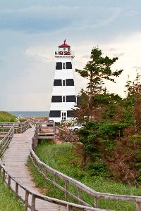 The boardwalk leads to the West Point Lighthouse as clouds move in, in the background.
