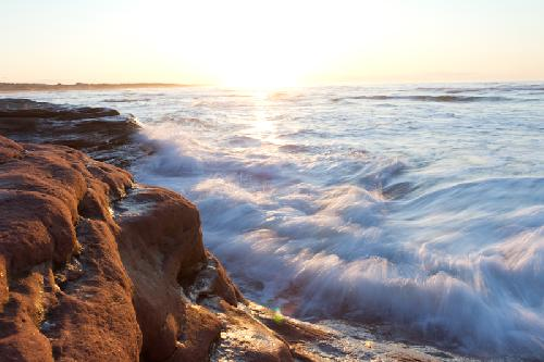Cavendish Beach waves crash into the rocks while the sun sets in the background
